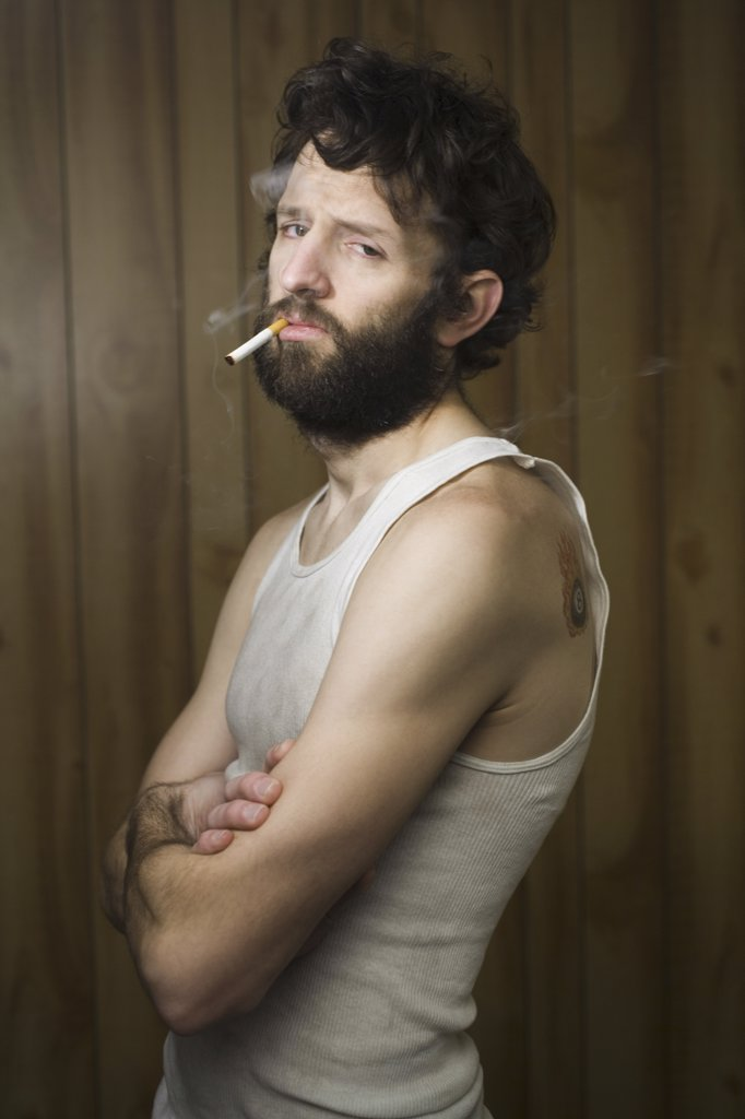 Man standing with cigarette and crossed arms : Stock Photo