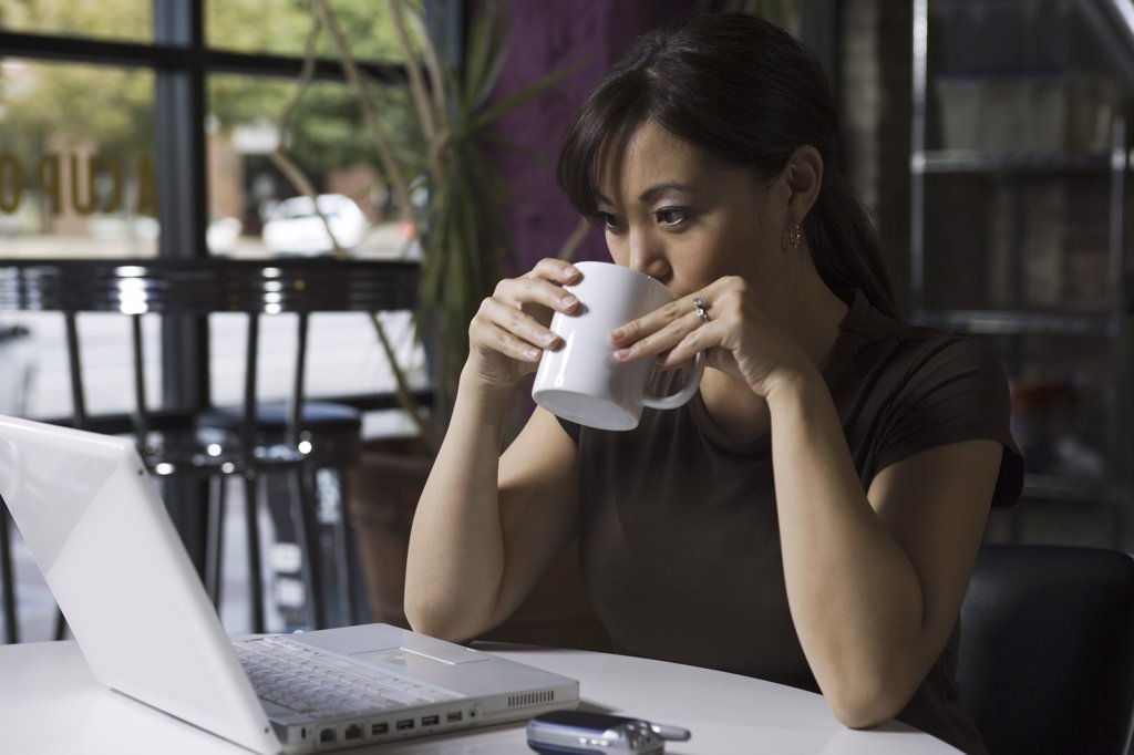 Young woman drinking coffee and working on a laptop : Stock Photo