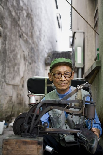 Stock Photo: 1660R-17865 Man with eyeglasses outdoor with shoe machine