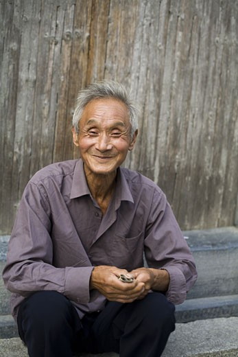 Old man sitting outdoors smiling : Stock Photo