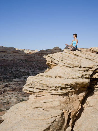 Stock Photo: 1660R-18256 Woman sitting cross legged on rock outdoors doing yoga