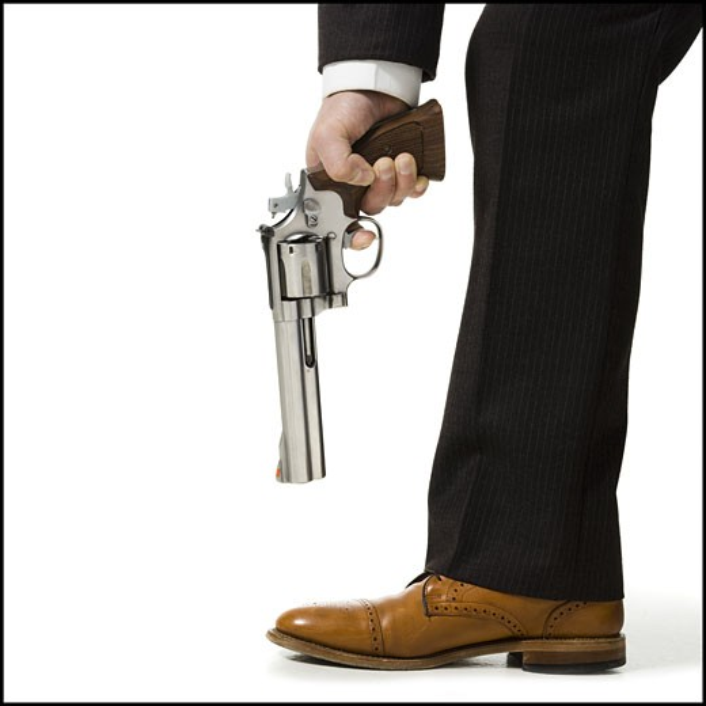 Stock Photo: 1660R-18362 Detailed view of man pointing shotgun at foot