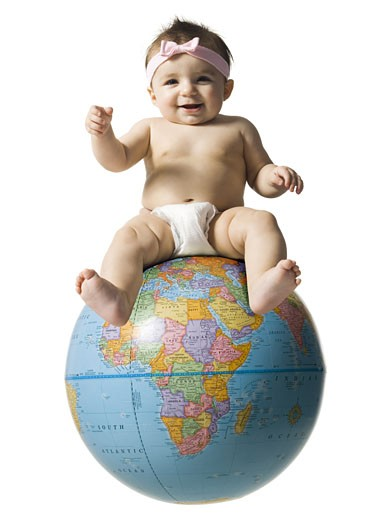 Stock Photo: 1660R-18376 Baby girl in diaper smiling and sitting on globe