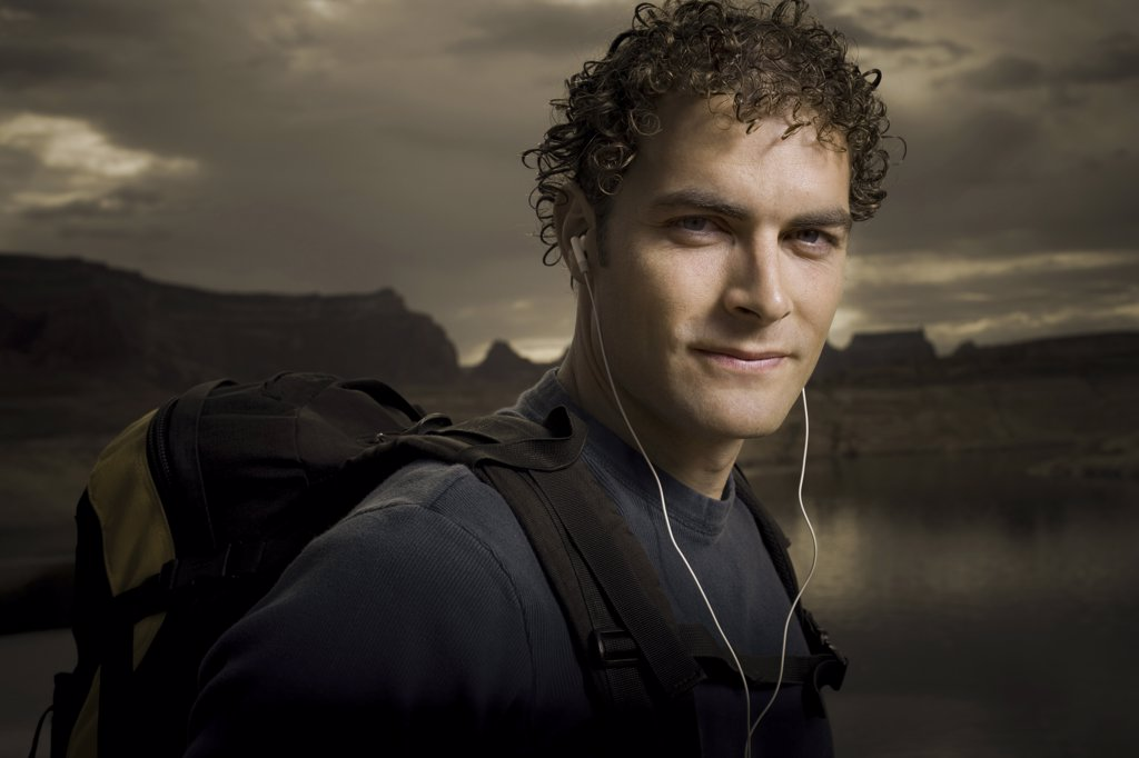 Stock Photo: 1660R-1838 Portrait of a young man wearing headphones and carrying a backpack