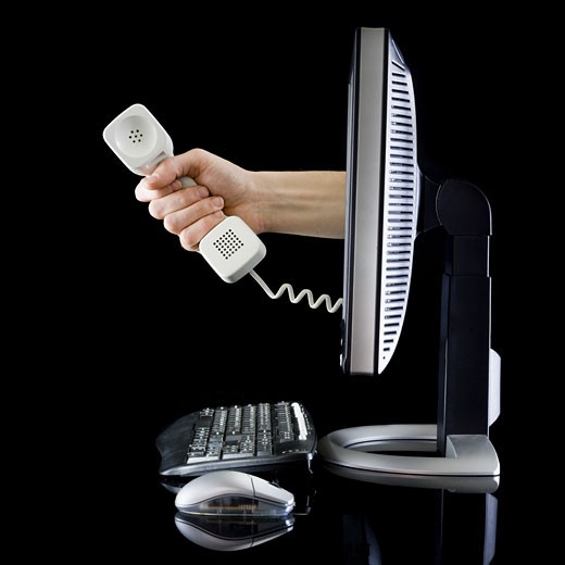 Stock Photo: 1660R-18386 Profile of computer with hand from monitor holding telephone receiver