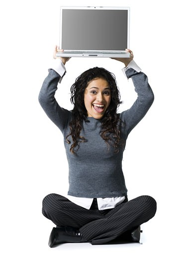 Stock Photo: 1660R-18513 Woman sitting cross legged with laptop smiling