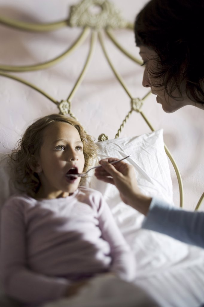 High angle view of a mother giving her daughter medicine : Stock Photo