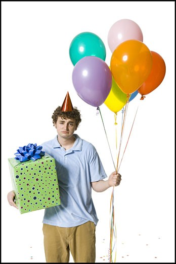 Man with party hat holding balloons and gift box looking sad : Stock Photo