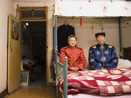 Stock Photo: 1660R-19004 Older couple sitting in room with bed