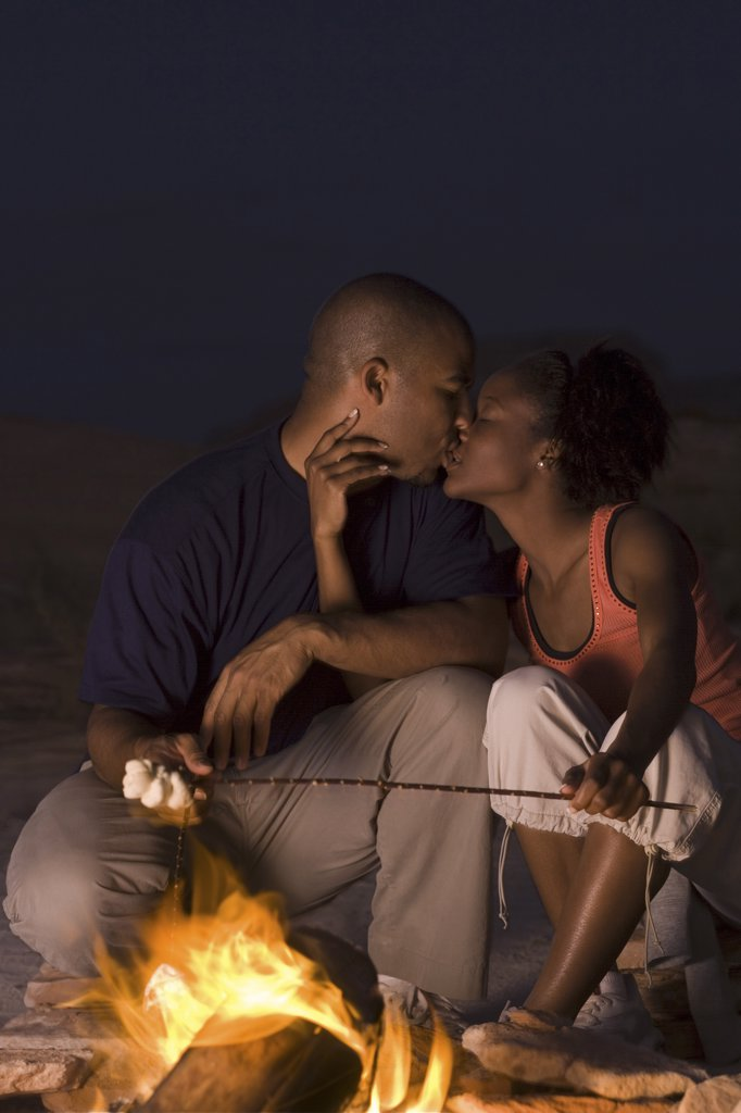 Stock Photo: 1660R-1905 Young couple kissing by a campfire