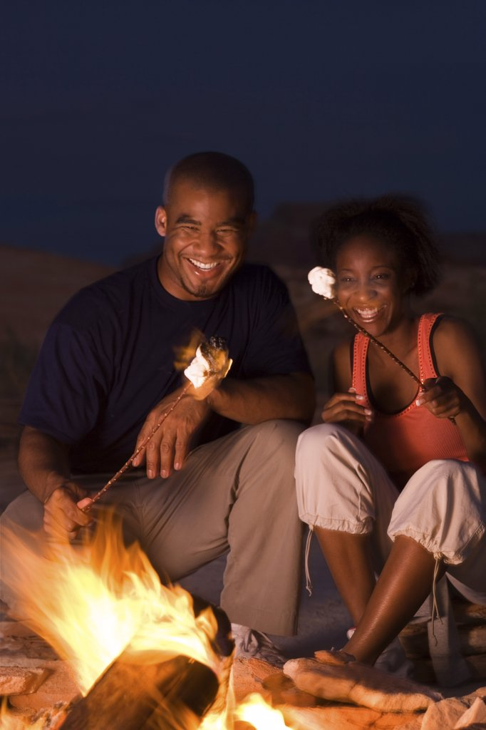 Young couple sitting by a campfire : Stock Photo