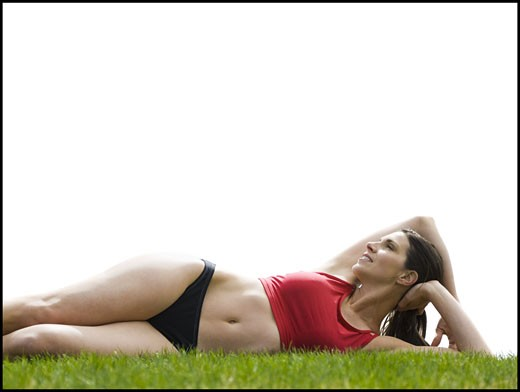 Woman in bikini lying down in grass : Stock Photo