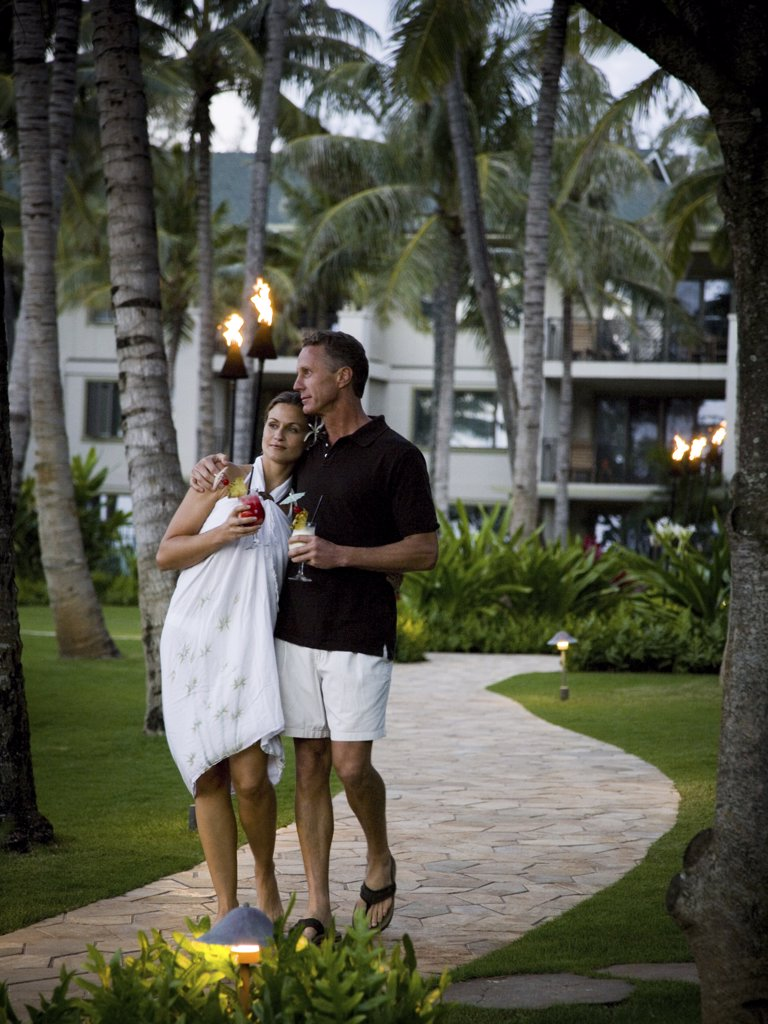 Stock Photo: 1660R-19373 Couple with tropical cocktails walking at resort