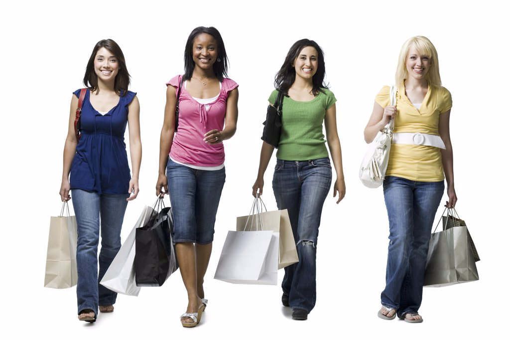 Four women walking and smiling with shopping bags : Stock Photo