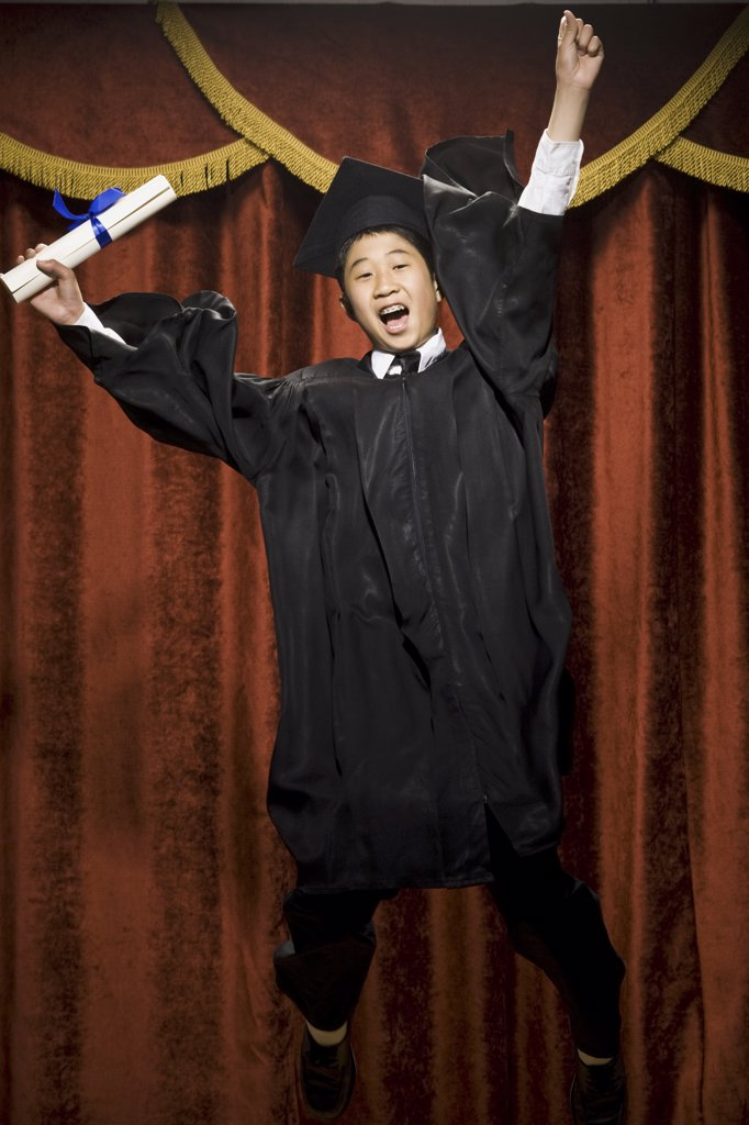 Boy graduate with mortar board and diploma smiling with braces and cheering : Stock Photo
