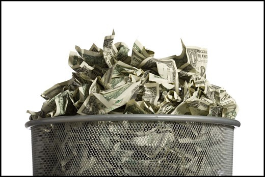 Waste paper basket with crumpled money : Stock Photo