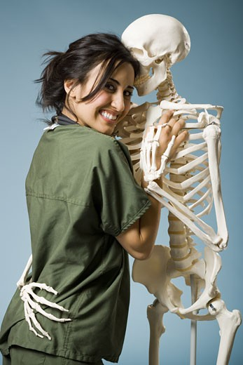 Woman in scrubs dancing with skeleton : Stock Photo