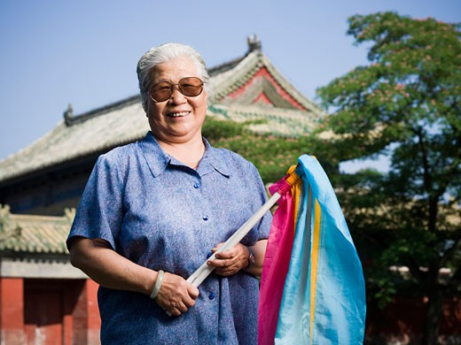 Woman standing outdoors with fabric on sticks with pagoda in background smiling : Stock Photo