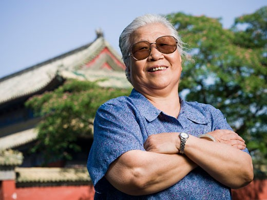 Stock Photo: 1660R-20233 Mature woman standing outdoors with arms crossed smiling