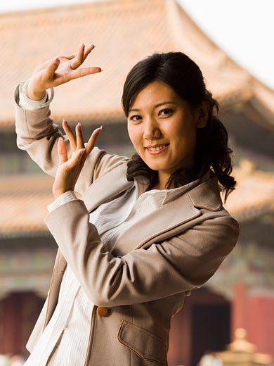 Stock Photo: 1660R-20404 Businesswoman doing tai chi outdoors smiling