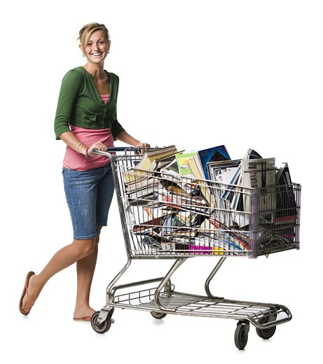 Woman with shopping cart filled with books smiling : Stock Photo