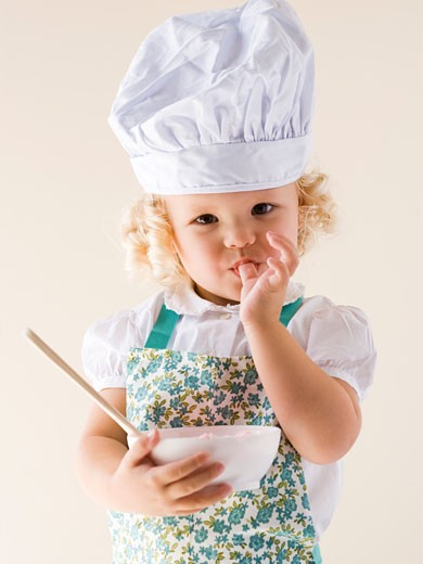 Stock Photo: 1660R-20698 Little girl wearing a chef's hat and holding a bowl.