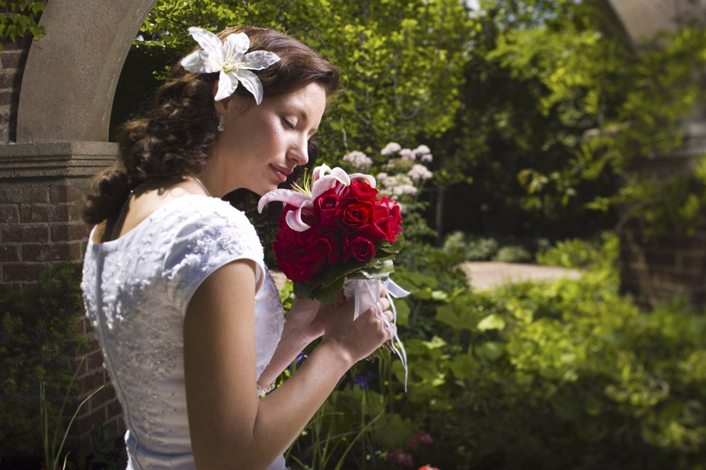 Stock Photo: 1660R-2083 Side profile of a young woman smelling flowers