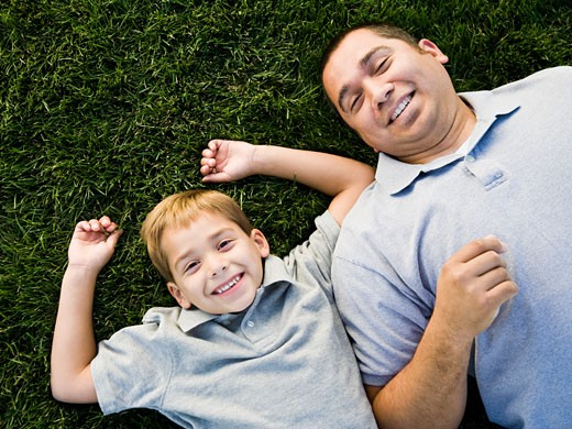 Stock Photo: 1660R-22139 dad and son lying on the grass.