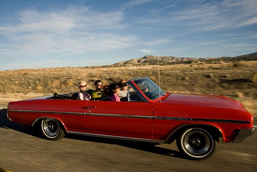 red car driving down the road : Stock Photo