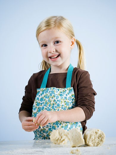 Stock Photo: 1660R-22931 little girl kneading dough