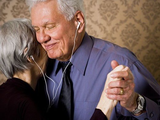 Profile of an elderly couple dancing and listening to music : Stock Photo