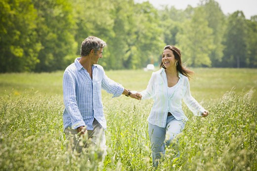 Mature man and a mid adult woman holding hands and running in a field : Stock Photo