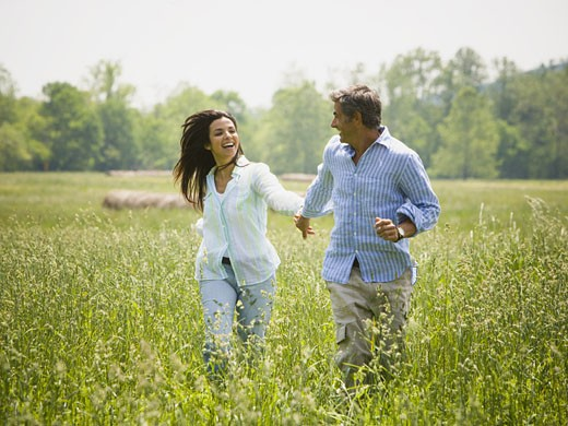 Stock Photo: 1660R-24664 Mature man and a mid adult woman holding hands and running in a field