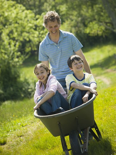 Stock Photo: 1660R-24705 Man pushing his son and daughter in a wheelbarrow