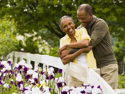 Senior man embracing a senior woman from behind : Stock Photo