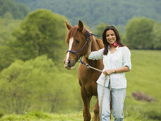 Portrait of a woman standing with a horse : Stock Photo