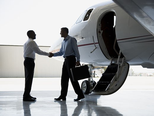 Profile of two businessmen shaking hands by an airplane : Stock Photo