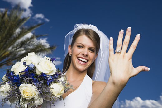 Portrait of a bride showing her wedding ring and smiling : Stock Photo