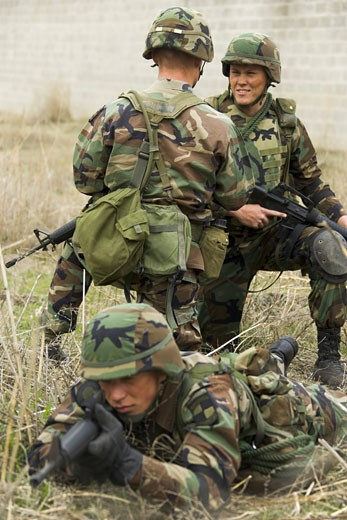 Soldier aiming his rifle with two soldiers talking behind him : Stock Photo