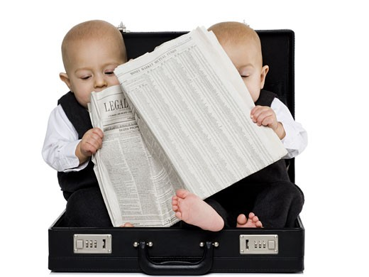 Stock Photo: 1660R-25063 Twin boys sitting in a briefcase with newspaper