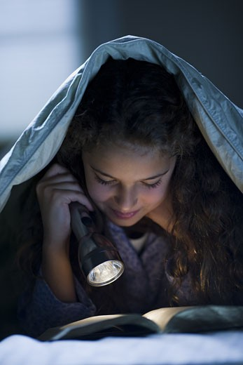 Stock Photo: 1660R-25395 Girl laying in bed under blanket with flashlight reading