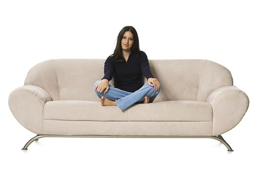 Portrait of a young woman sitting on a couch : Stock Photo