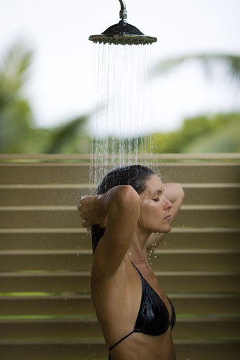 Profile of an adult woman taking a shower : Stock Photo