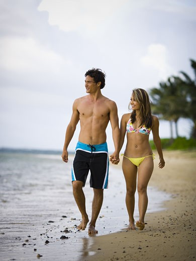 Stock Photo: 1660R-26448 Young couple holding hands and walking on the beach