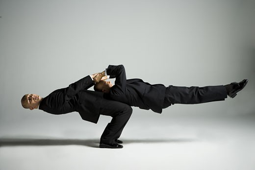 Stock Photo: 1660R-26710 Profile of two male acrobats in business suits performing