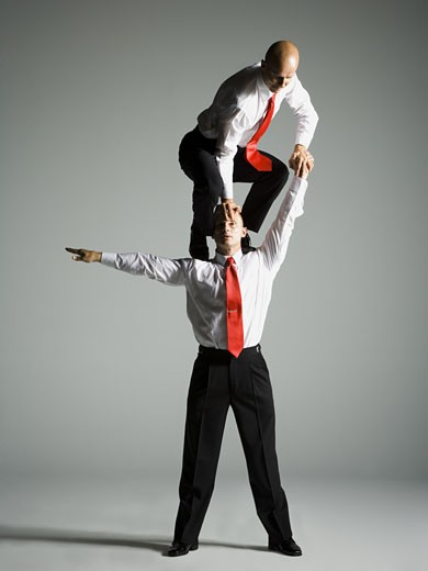Two male acrobats in business suits performing : Stock Photo
