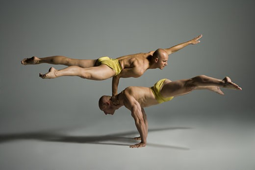 Stock Photo: 1660R-26734 Profile of two male acrobats performing
