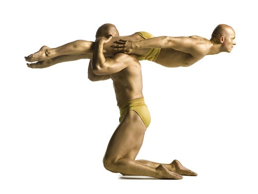 Profile of two male acrobats performing : Stock Photo