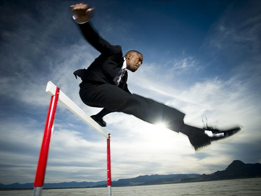 Stock Photo: 1660R-26774 Low angle view of a businessman jumping over a hurdle in a race