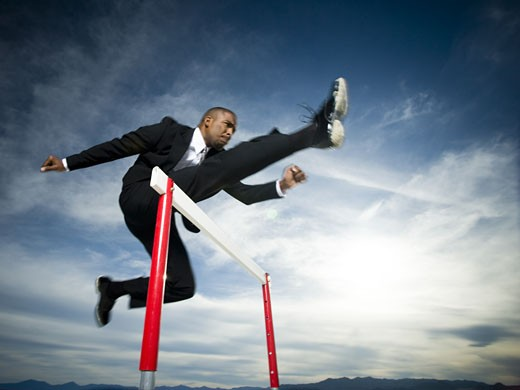 Stock Photo: 1660R-26775 Low angle view of a businessman jumping over a hurdle in a race